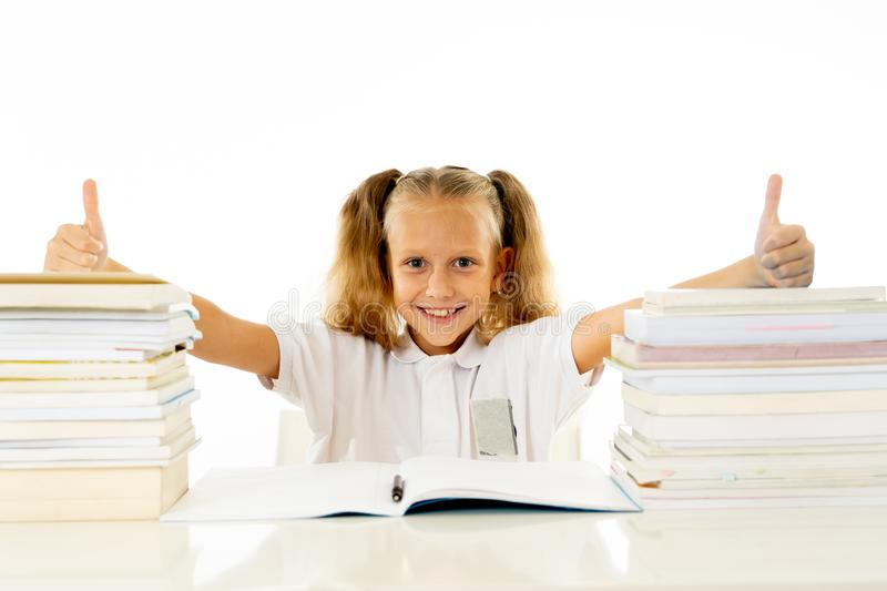 Happy beautiful cute with blond hair little schoolgirl likes studying and reading books in creative education concept with Back to. School theme isolated on royalty free stock photography