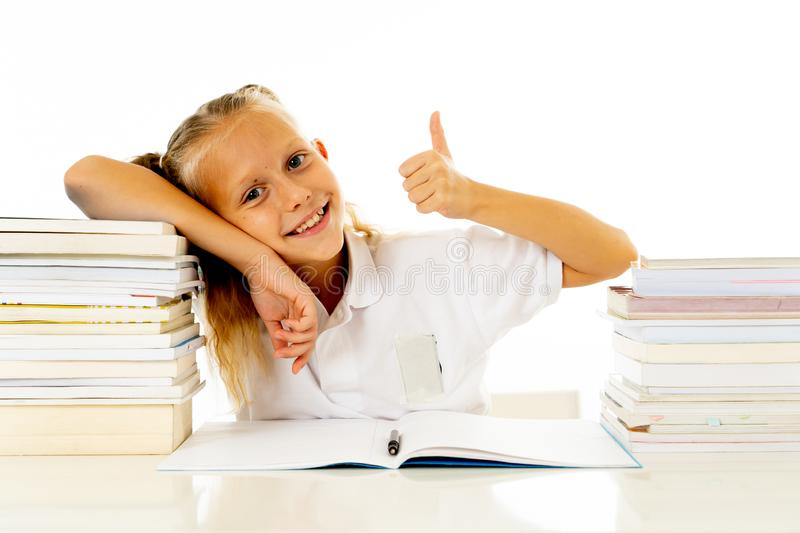 Happy beautiful cute with blond hair little schoolgirl likes studying and reading books in creative education concept with Back to. School theme isolated on royalty free stock image