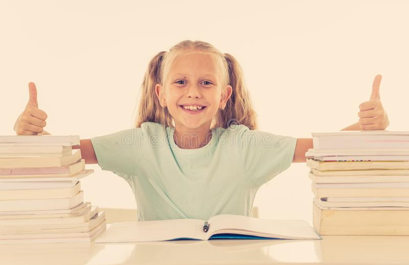 Happy beautiful cute with blond hair little schoolgirl likes studying and reading books in creative education concept with Back to. School theme isolated on royalty free stock photos