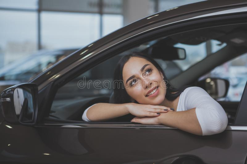 Lovely young woman buying new car at the dealership. Happy beautiful dark haired woman buying new automobile at the dealership, sitting in a car looking away royalty free stock images