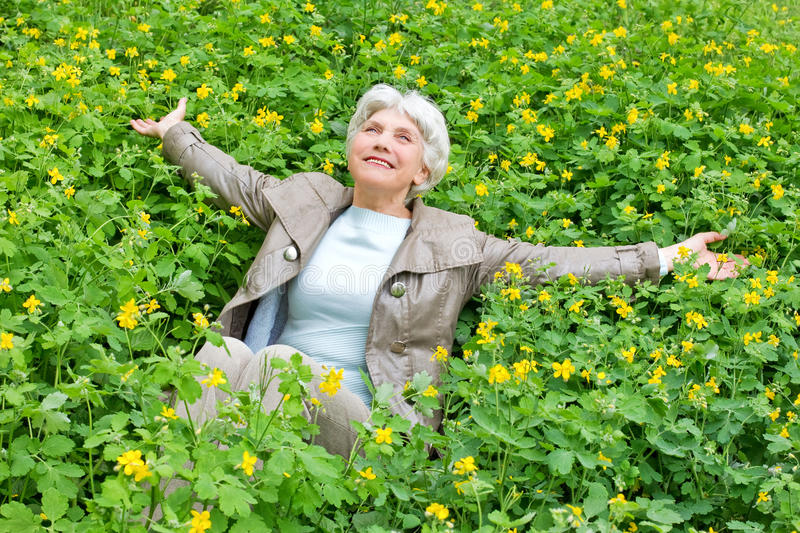Happy beautiful elderly woman sitting on a glade of yellow flowers in spring. Happy beautiful elderly woman sitting arms outstretched on a glade of yellow royalty free stock image