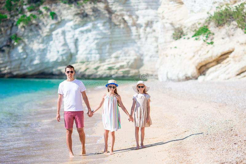 Happy beautiful family of dad and kids on white beach. Kids with his father walk on the beach together royalty free stock image