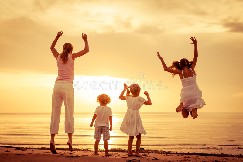 Happy beautiful family dancing on the beach. At the dawn time stock photos