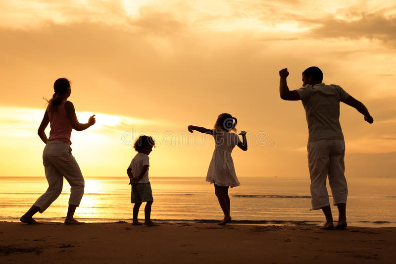 Happy beautiful family dancing on the beach. At the dawn time royalty free stock image