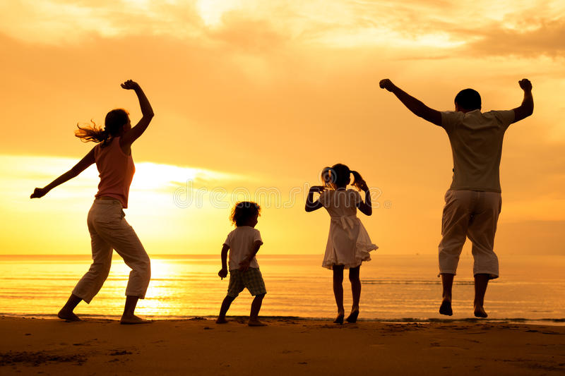 Happy beautiful family dancing on the beach. At the dawn time royalty free stock photography