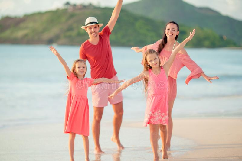 Happy family with kids walk on the beach at sunset. Happy beautiful family on white beach having fun royalty free stock photo