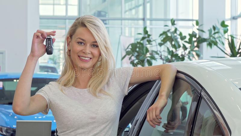 Happy beautiful female driver showing car keys to ker new automobile. Young attractive woman buying new car at the dealership, holding car keys, smiling to the stock photos