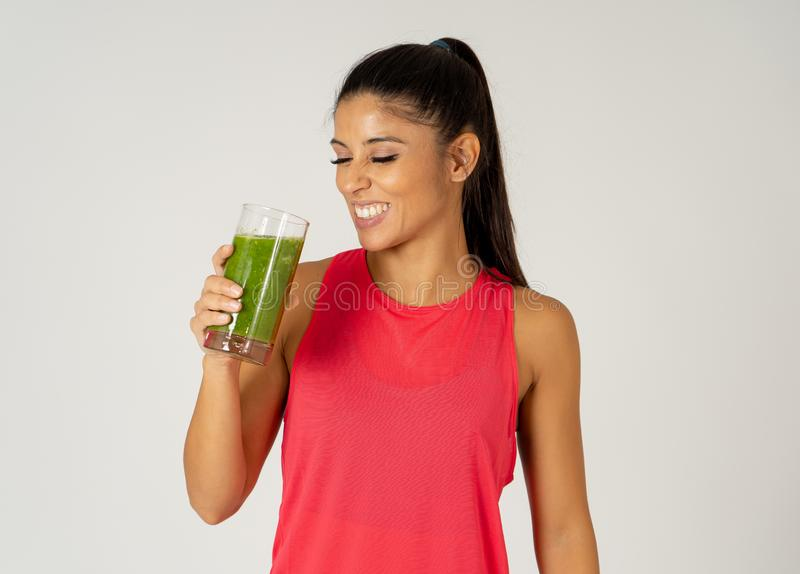 Happy beautiful fit sport woman smiling and drinking healthy fresh vegetable smoothie stock photography
