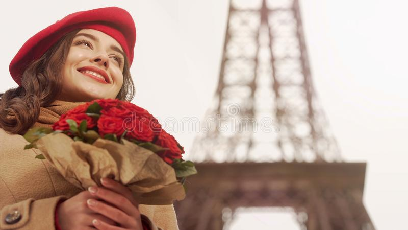 Happy beautiful girl admiring bouquet of red roses on background of Eiffel Tower stock image
