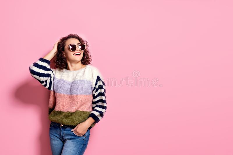 Happy beautiful girl with amazing toothy smile posing in fashionable sweater, jeans and sunglasses on pink pastel stock image