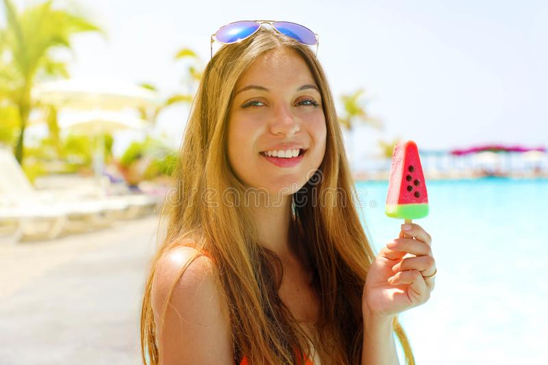 Happy beautiful girl eating popsicle ice pop in form of watermelon slice and looking at  camera. Summer holidays concept royalty free stock photos