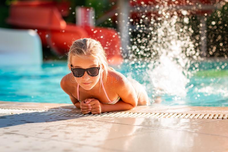 Happy beautiful girl having fun at the pool. At the resort stock photo