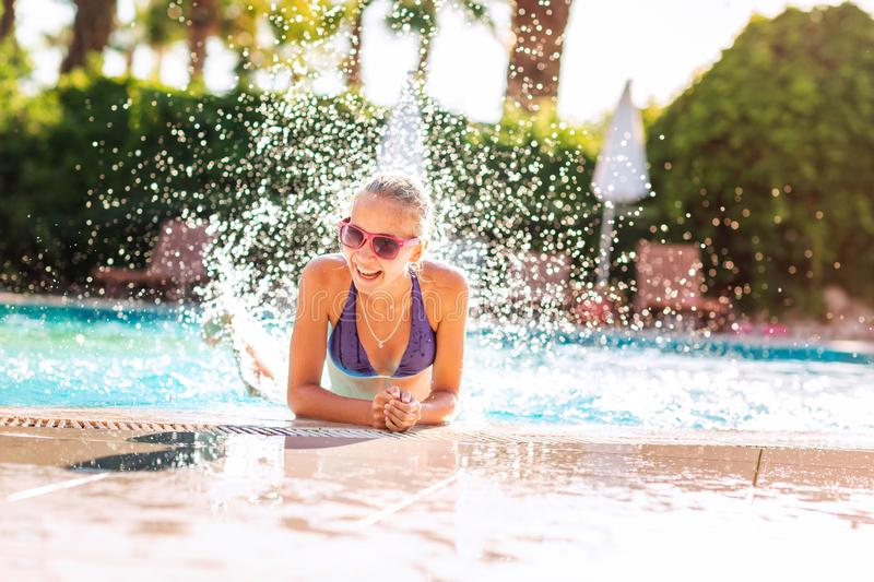 Happy beautiful girl having fun at the pool. At the resort royalty free stock photography