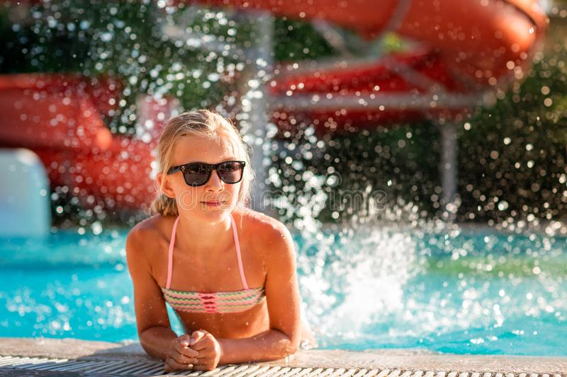 Happy beautiful girl having fun at the pool stock photo