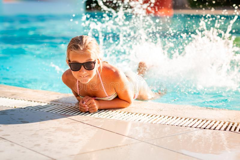 Happy beautiful girl having fun at the pool. At the resort stock image