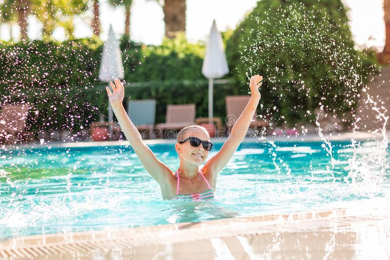 Happy beautiful girl having fun at the pool. At the resort stock photos