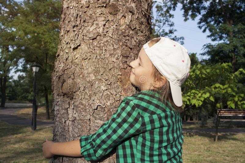 Happy beautiful girl hugging big tree in park . Loving nature . stock photo