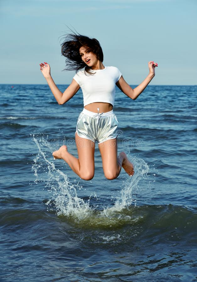 Happy beautiful girl  jump in the sea water royalty free stock images