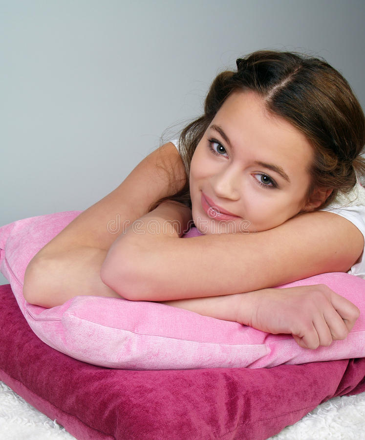 The happy beautiful girl lies on pink pillows royalty free stock photos