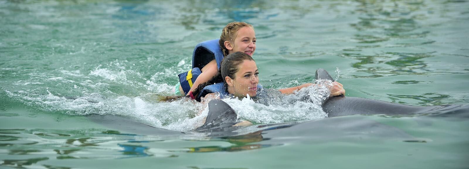 Happy beautiful girl and little daughter laughs and swims with dolphins stock photos