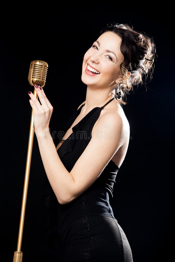 Happy beautiful girl singer laughing behind retro microphone. Beautiful young female vocalist in black evening dress happily laughing holding golden retro royalty free stock photos