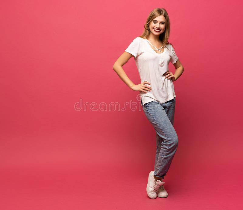 Happy beautiful girl standing in full length, isolated on pink background. royalty free stock photos