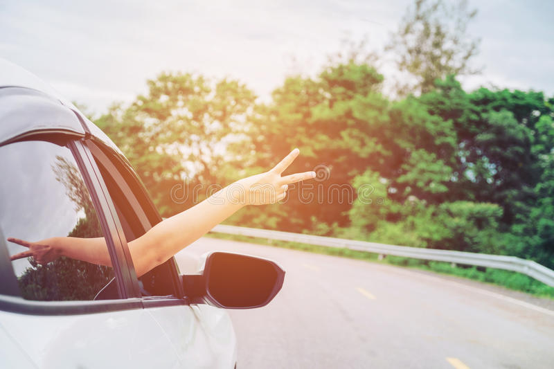 Happy beautiful girl traveling in a hatchback car royalty free stock photos