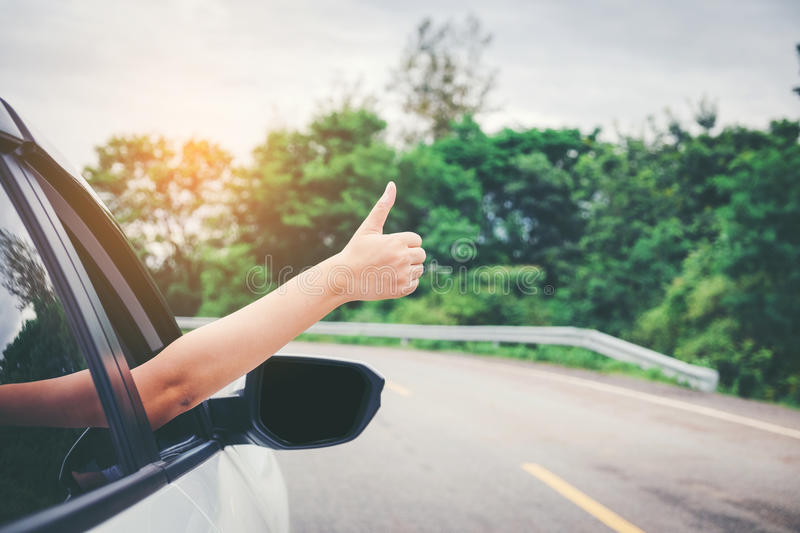 Happy beautiful girl traveling in a hatchback car stock image