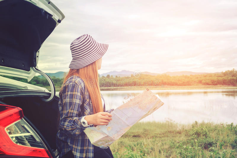 Happy beautiful girl traveling in a hatchback car with map royalty free stock photos