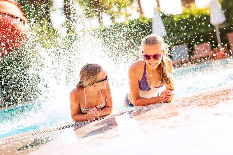 Happy beautiful girls having fun at the pool. At the resort stock photo