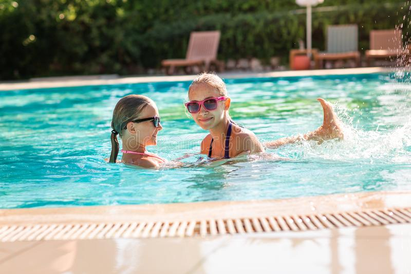 Happy beautiful girls having fun at the pool. At the resort royalty free stock image