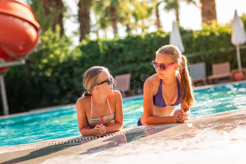 Happy beautiful girls having fun at the pool. At the resort stock photography