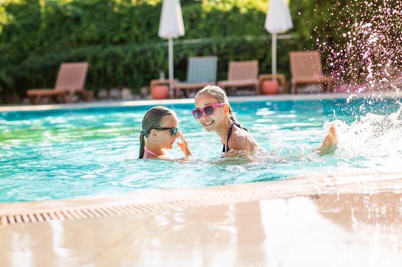 Happy beautiful girls having fun at the pool royalty free stock photo
