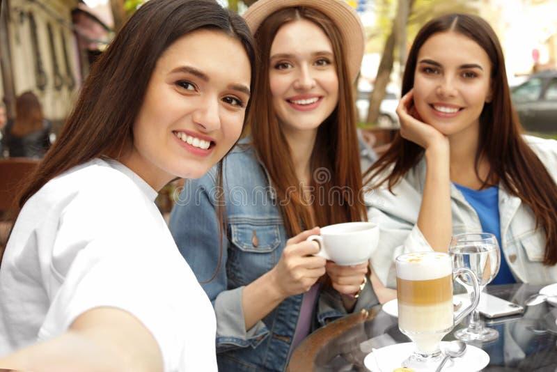 Happy beautiful girls taking selfie in cafe royalty free stock photo