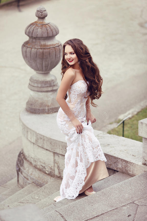 Happy beautiful gorgeous bride laughing and running on steps, we royalty free stock photography