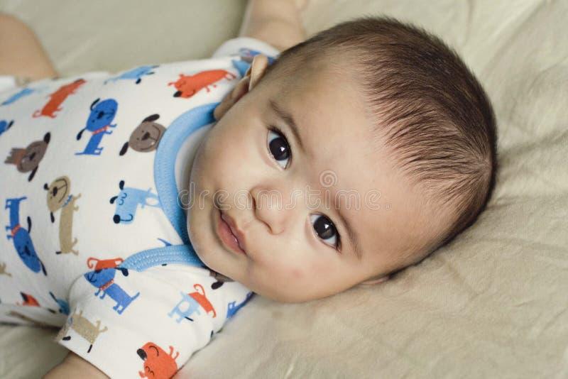 Happy beautiful hispanic baby boy relaxing. Happy and beautiful hispanic baby boy relaxing on his bed stock image