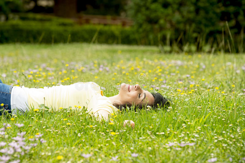 Happy beautiful latin woman lying on the green grass sleeping and meditating stock images
