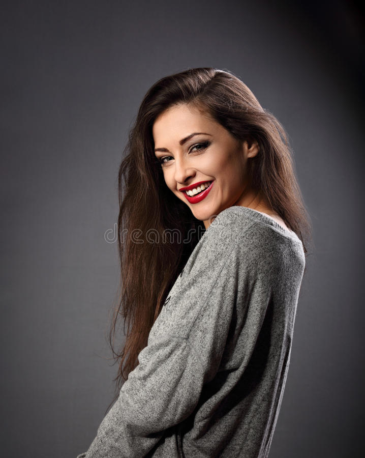 Happy beautiful laughing woman with long hair style in grey fashion sweater looking with toothy smiling on dark shadow background stock photography