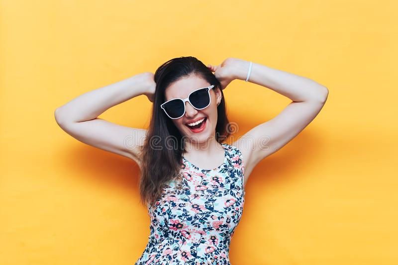 Happy beautiful laughing yound woman in dress and white sunglasses on yellow background royalty free stock photos