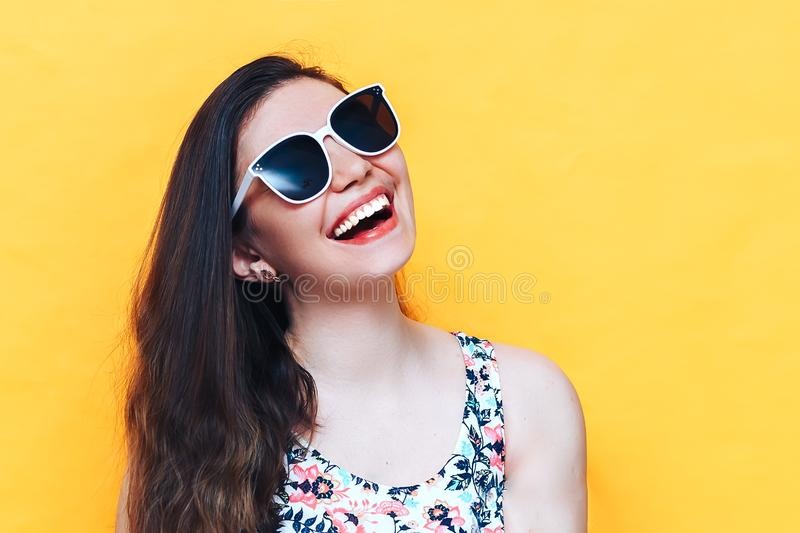 Happy beautiful laughing yound woman in dress and white sunglasses on yellow background royalty free stock photo