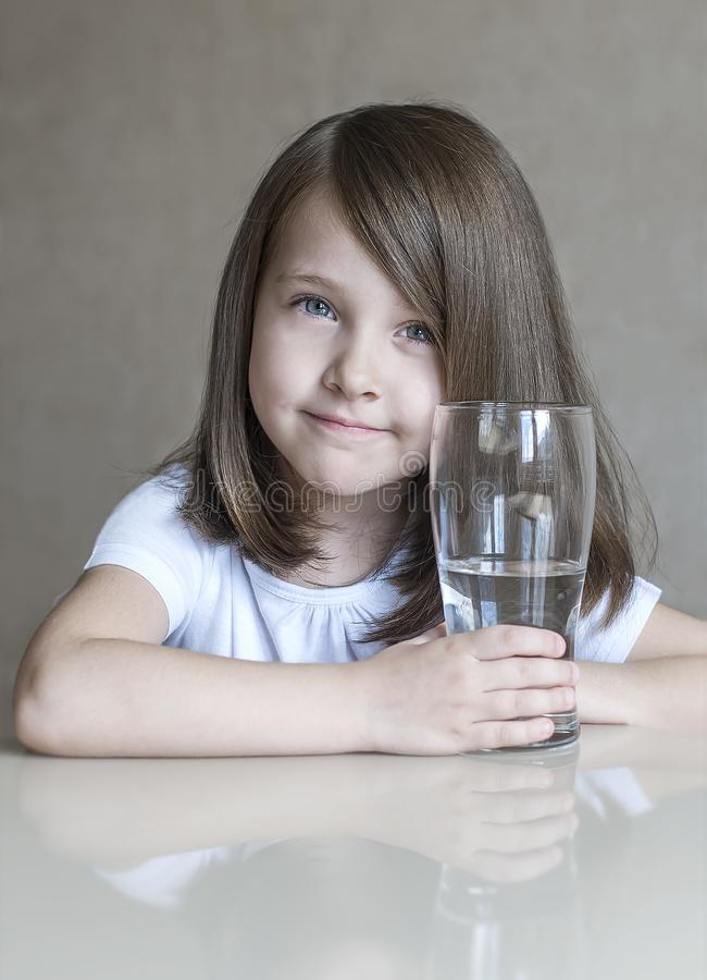 Happy beautiful little girl drinking clear water. Portrait of smiling baby holding transparent glass royalty free stock image