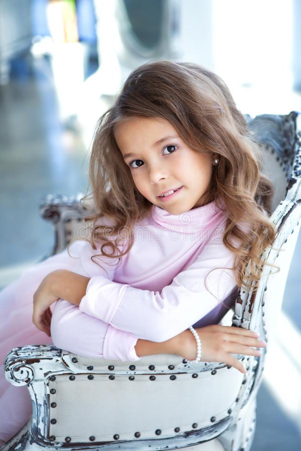 Happy little girl is sitting in the light studio royalty free stock photo