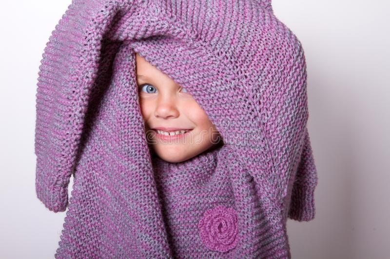 Happy beautiful little girl wore a knitted lilac mom`s sweater stock image