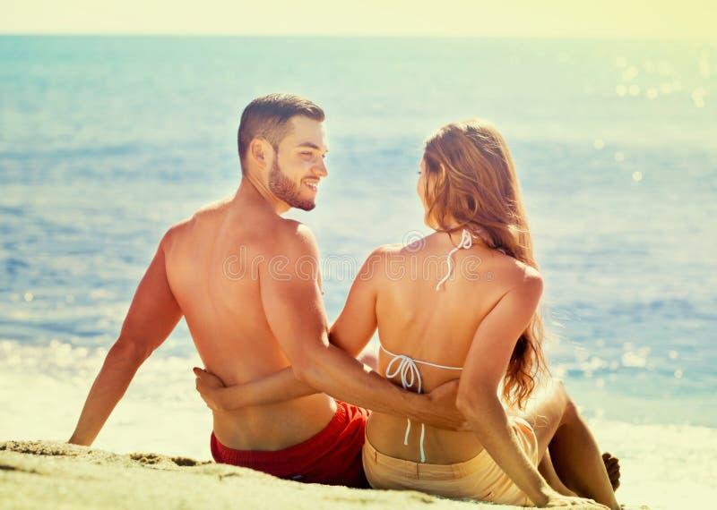 Happy beautiful lovers sunbathing. At sandy beach in honeymoon royalty free stock images