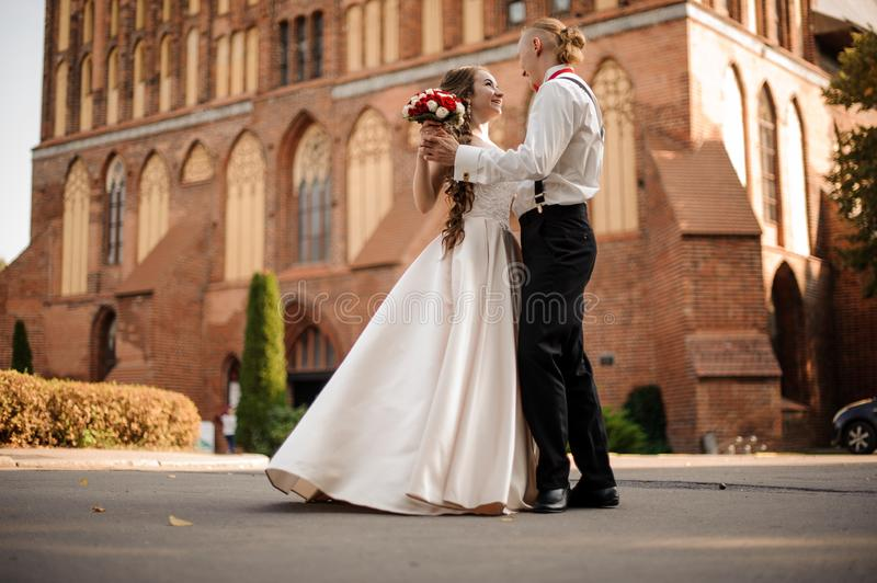 Happy and beautiful married couple dancing in the background of vintage red brick building with royalty free stock photography