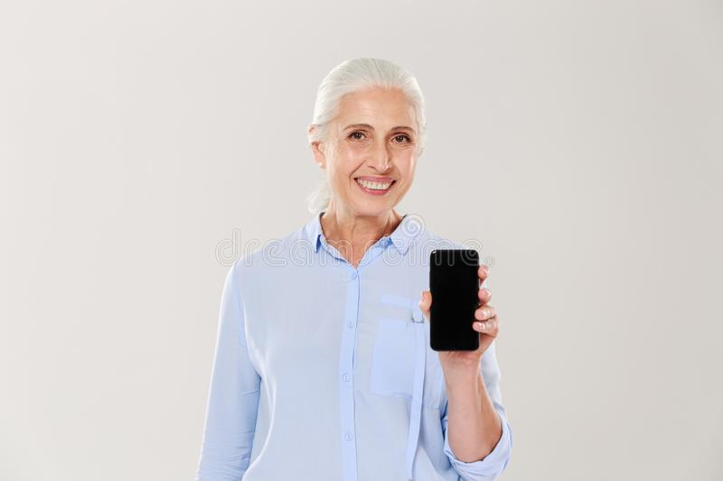 Happy beautiful mature woman showing smartphone with blank black screen isolated. Happy beautiful mature woman in blue shirt showing smartphone with blank black stock image