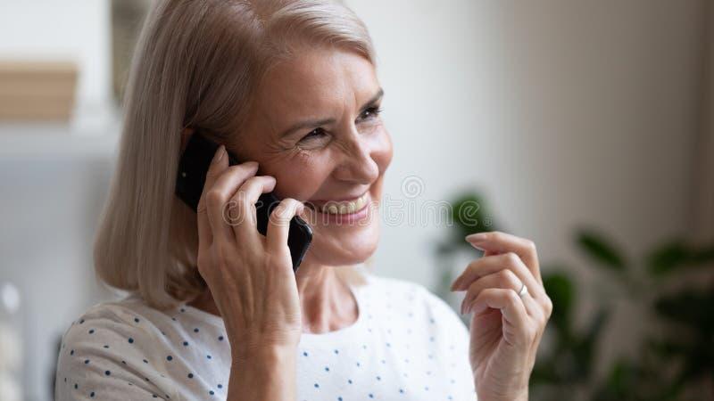Happy beautiful mature woman making phone call close up royalty free stock photos