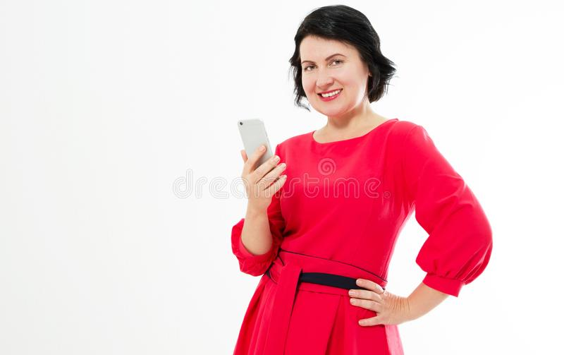 Happy beautiful middle-aged woman in red dress uses her phone. Charming brunette woman chatting on the internet royalty free stock photos