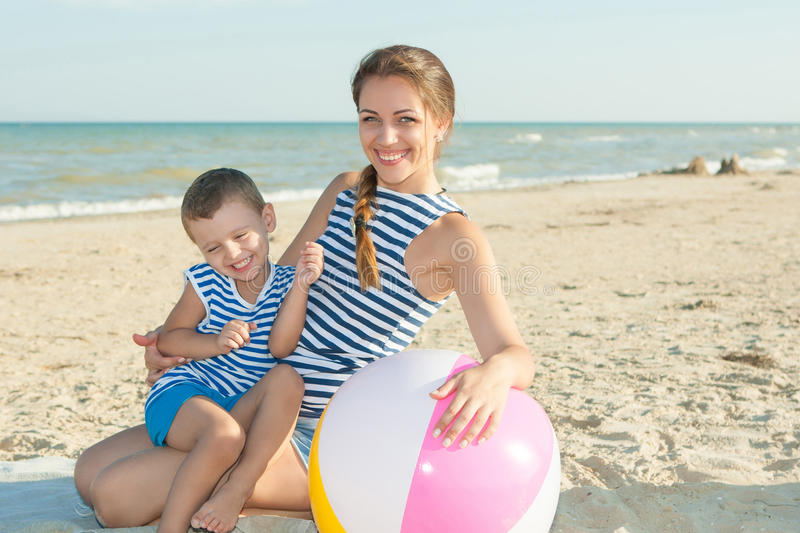 Happy beautiful mother and son enjoying beach time royalty free stock photography