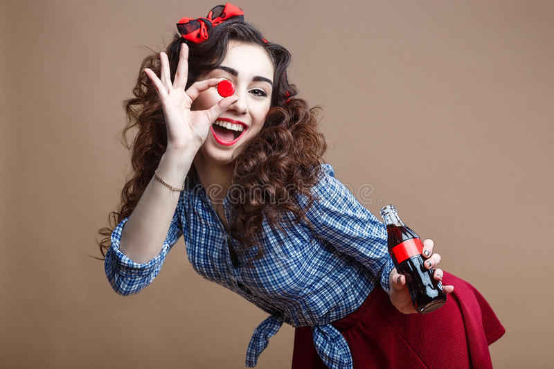 Happy beautiful pin up girl holding cup of glass bottle and giving you a soda. Woman dressed in red shirt and blue plaid. Happy Beautiful Pin Up Girl Holding Cup stock photography